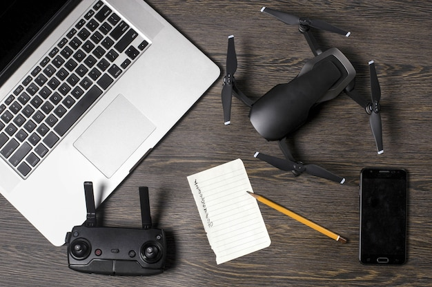 Quadrocopter auf hölzernem hintergrund, zubehör für drohnen, telefon und laptop in der nähe des blattes zum erstellen einer liste von orten für luftaufnahmen