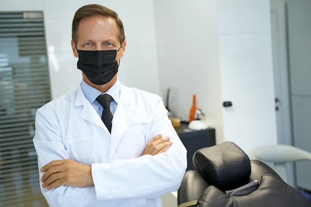 Qualifizierte zahnärztin posiert mit maske