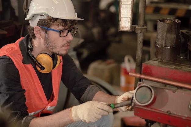 Qualifizierter manueller arbeiter der jungen amerikanischen industrie, der als technikeringenieur maschinenreparaturreparaturwartung in fabrik arbeitet.