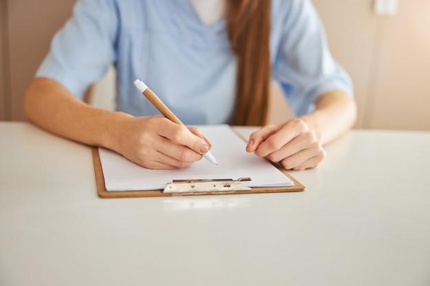 Qualifizierter medizinischer mitarbeiter, der notizen auf papier schreibt