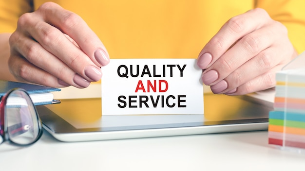 Qualität und service sind auf einer weißen visitenkarte in den händen einer frau geschrieben. brillen tablette und block mit mehrfarbigem papier für notizen