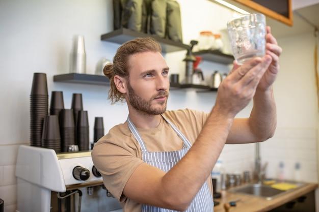 Qualitätskontrolle. aufmerksamer junger bärtiger mann im t-shirt und in der schürze, die glas in erhobenen händen nahe kaffeemaschine betrachten