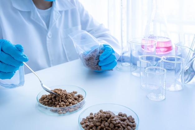 Qualitätskontrollpersonal prüft die qualität von heimtierfutter. qualitätskontrolle in der tierfutterindustrie.
