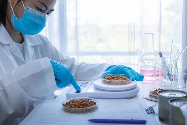 Qualitätskontrollpersonal wiegt trockenfutter für haustiere, um die qualität zu überprüfen. physische qualitätsprüfung. qualitätskontrollprozess der tiernahrungsindustrie.