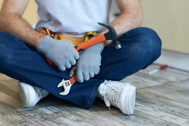 Qualitätsreparatur beschnittener schuss eines jungen mechanikers, der einen hammer und einen verstellbaren schraubenschlüssel in seinem hält