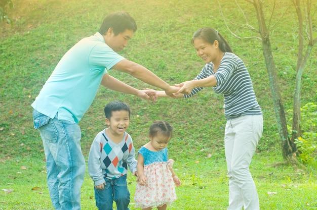 Qualitätszeitgenuss der asiatischen familie im freien, asiatische leute, die während des schönen sonnenuntergangs spielen.