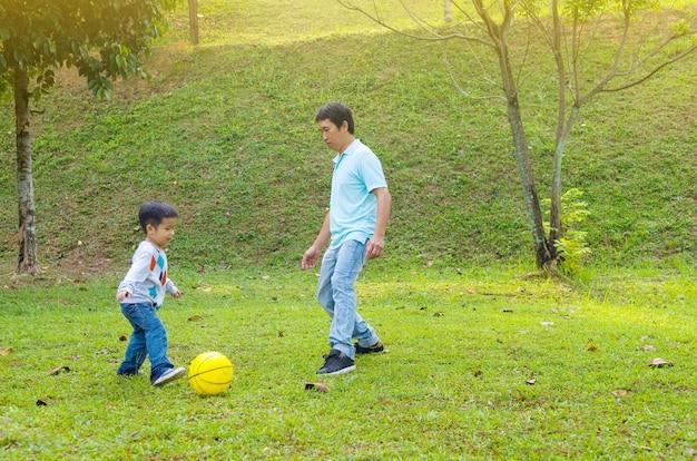 Qualitätszeitgenuss des asiatischen vaters und des sohns im freien, asiatisches leutespielen