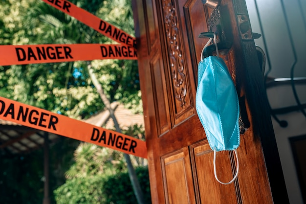 Quarantäne. coronavirus pandemie. der eingang zur straße ist mit roten warnbändern verschlossen - gefahr. schutzmaske.