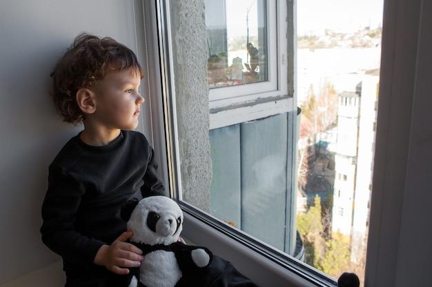 Quarantäne. ein kleiner junge sitzt auf einem fensterbrett und schaut gelangweilt aus dem fenster. sehnsucht nach frischer luft und spaziergänge entlang der straße. zwangsheim während der quarantäne aufgrund der coronavirus-pandemie