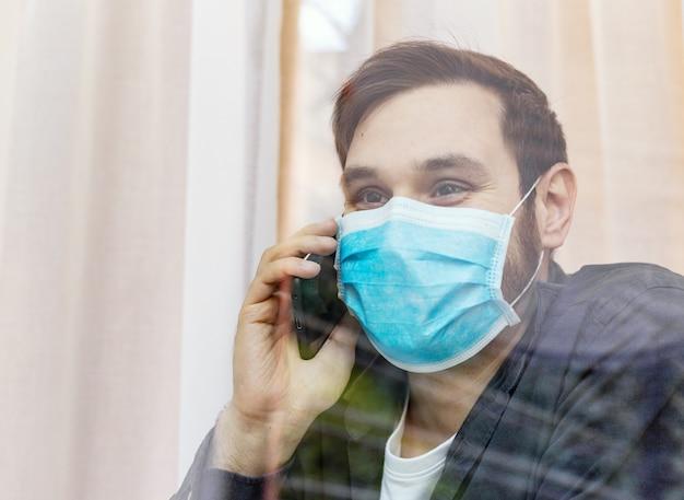 Quarantäne einsamer mann mit covid-19 in isulation telefoniert mit der familie, blick in das fenster. prävention von coronavirus-pandemien. mann in schützender medizinischer maskenquarantäne. medizin-gesundheitskonzept
