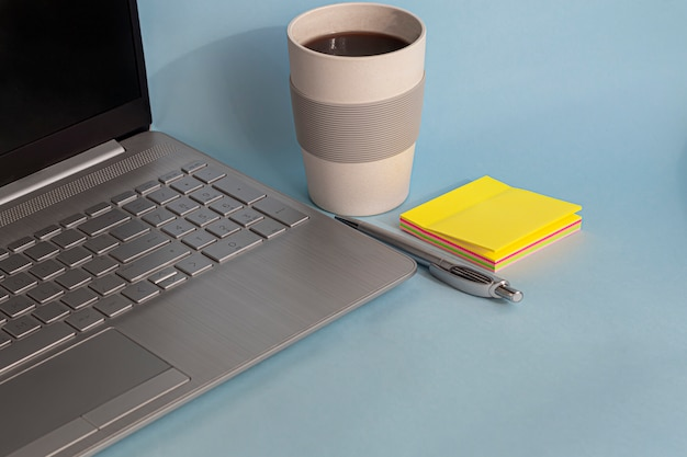 Quarantäne, online-schulung, arbeit von zu hause aus. laptop, telefon und stift, aufkleber und kaffee in einem wiederverwendbaren glas. coronavirus-pandemie in der welt. büros und schulen schließen.