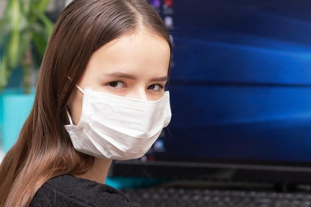 Quarantäne- und coronavirus-gefahr. eine junge frau in einer antibakteriellen maske arbeitet an einem computer