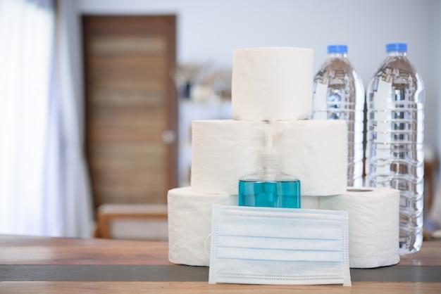 Quarantäne zu hause aufgrund von coronavirus- oder covid-19-schutz mit handgel, taschentuchrolle, trinkwasserflasche und blauer maske im wohnzimmer