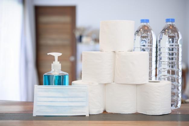 Quarantäne zu hause aufgrund von coronavirus- oder covid-19-schutz mit handgel, taschentuchrolle, trinkwasserflasche und op-maske im wohnzimmer