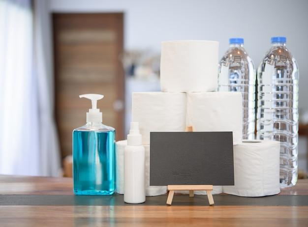 Quarantäne zu hause aufgrund von coronavirus- oder covid-19-schutz mit handgel, taschentuchrolle, trinkwasserflasche und tafelschild im wohnzimmer