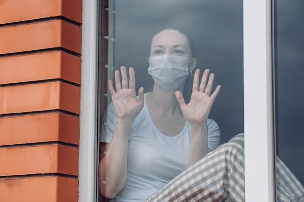 Quarantäne zu hause. die kaukasische frau, die am fenster in einer medizinischen maske sitzt und hinausschaut, will hinausgehen. schutz gegen coronavirus-infektion.