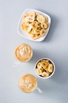 Quarantäneküche. zwei tassen mit dalalgonakaffee und bananenchips auf grauem hintergrund. draufsicht. vertikal