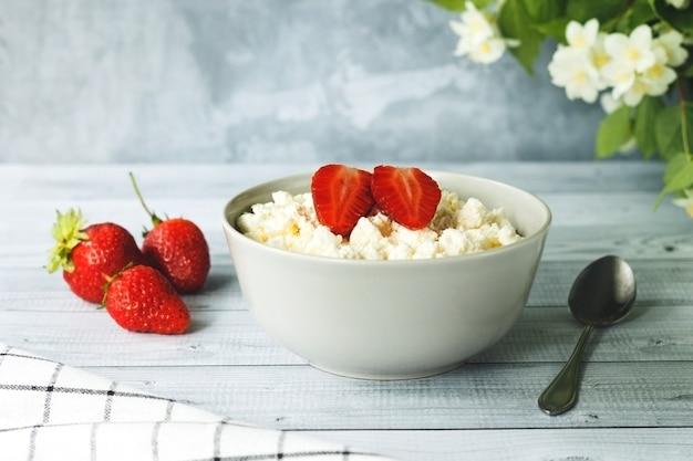 Quark oder hüttenkäse in schüssel mit erdbeeren