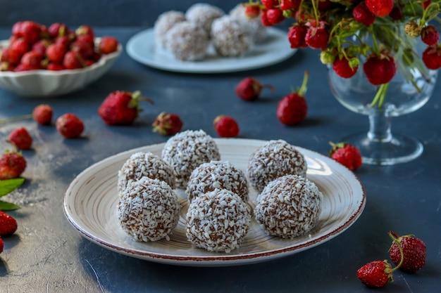 Quarkbällchen mit kokosnussspänen, erdbeeren und schokoladenkeksen auf einer dunklen oberfläche, horizontal