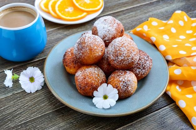 Quarkbällchen pommes zum frühstück. frisch zubereitete donuts mit puderzucker. dessert aus dem hüttenkäse