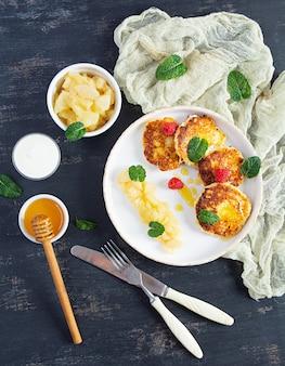 Quarkpfannkuchen mit sauerrahm, honig und beeren. leckeres syrniki mit karamellisierten birnen. ansicht von oben