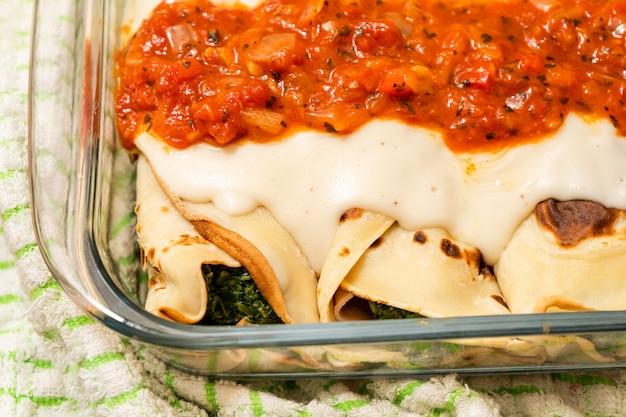 Quelle für hausgemachte spinat-cannelloni mit bechamelsauce und filet. konzept der hausmannskost, gesunde ernährung, natürlich.