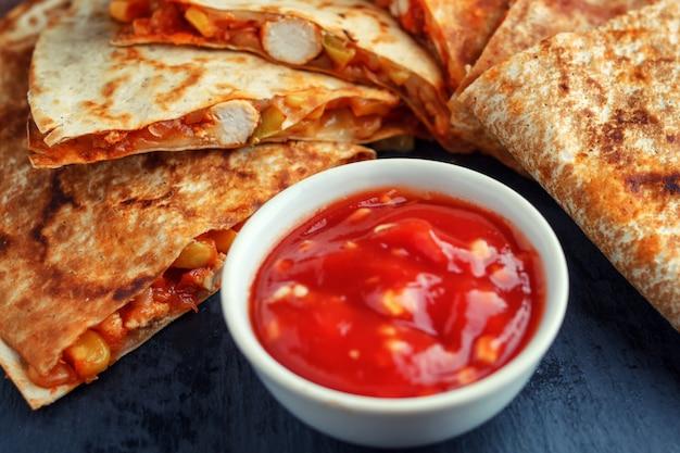 Quesadilla mit salsasoße auf einem hölzernen hintergrund