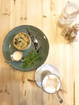 Quiche lorraine mit wurst und rucola auf dem teller und latte-kaffee auf dem tisch im restaurant