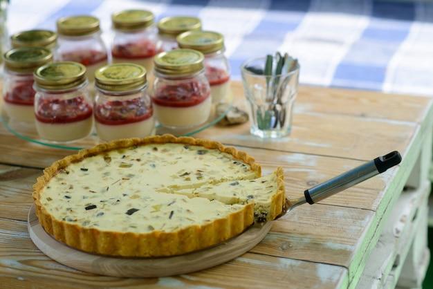 Quiche lorraine pie mit geschnittener scheibe auf einem holztisch mit gläsern mit pannacotta.