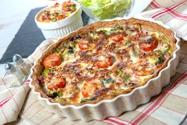 Quiche mit brokkoli, käse und tomaten auf handtuch