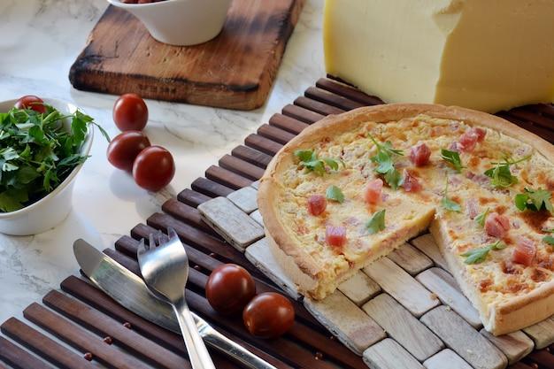 Quiche mit schinken und käse auf einer marmortabelle mit petersilie und tomate
