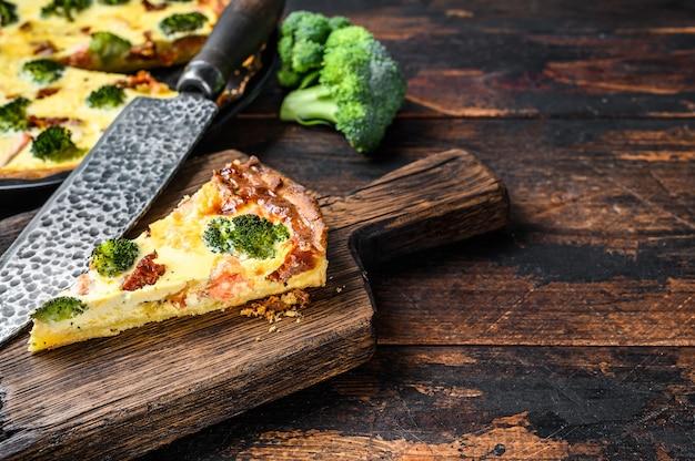 Quiche-torte mit räucherlachs, brokkoli und spinat. dunkler hölzerner hintergrund. draufsicht. speicherplatz kopieren.