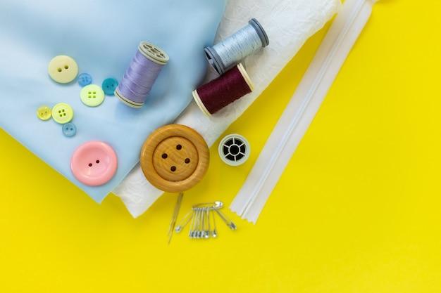 Quilt-, stick- und nähwerkzeuge auf dem tisch. , zahnseide, reifen. stoffmaterialien auf gelbem hintergrund. flatlay-kopierraum