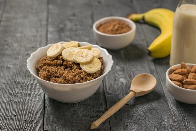 Quinoa brei mit bananen- und mandelmilch auf einem holztisch