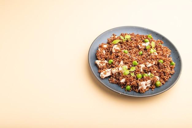 Quinoa-brei mit erbse und huhn auf keramikplatte auf einer pastellorangen oberfläche