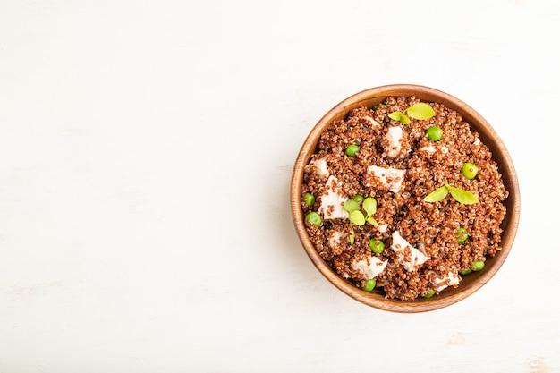 Quinoa brei mit erbse und huhn in holzschale