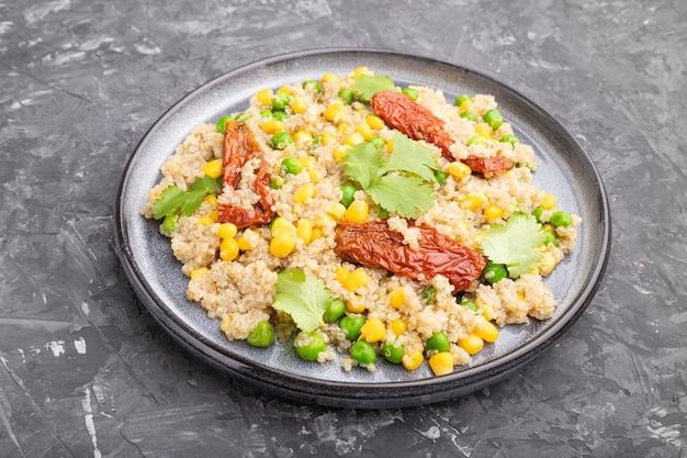 Quinoa-brei mit erbsen, mais und getrockneten tomaten