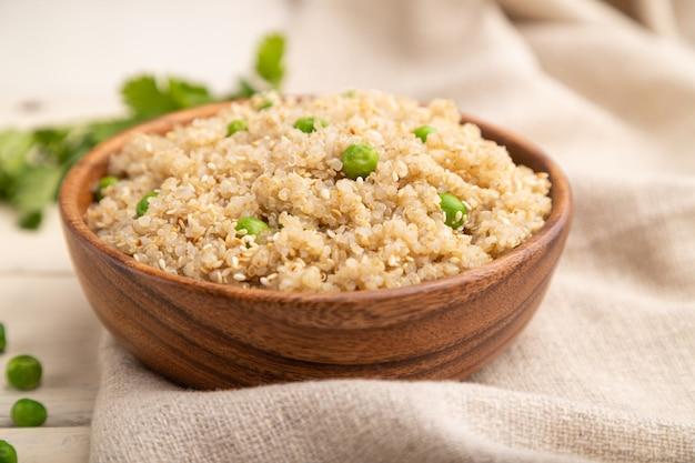 Quinoa brei mit grüner erbse in holzschale auf einer weißen holzoberfläche und leinen textil