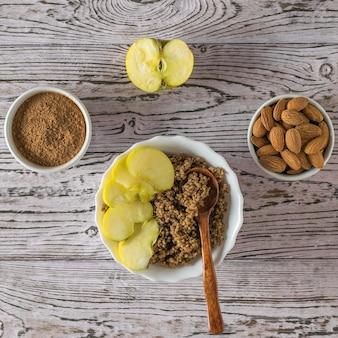 Quinoa brei mit kakao und apfel auf dem tisch. gesunde ernährung. flach liegen.