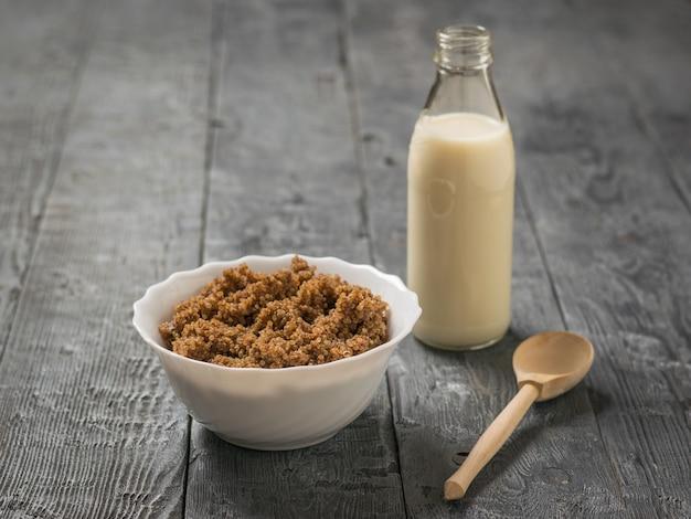 Quinoa brei mit kakao und einer flasche mandelmilch auf einem holztisch. gesunde ernährung.