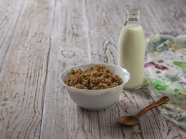 Quinoa brei mit kakao und mandelmilch auf einem holztisch mit einem stück stoff. gesunde ernährung.