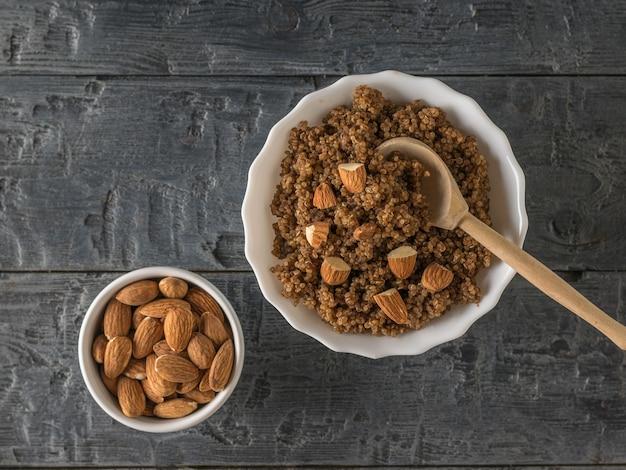 Quinoa brei mit kakao und mandeln auf einem schwarzen holztisch. gesunde ernährung.