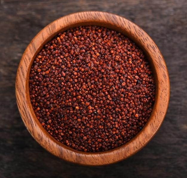 Quinoa in der schüssel auf holztisch. draufsicht