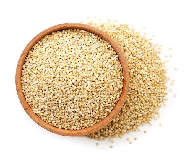 Quinoa in einer holzplatte nahaufnahme auf weißem hintergrund, isoliert. die aussicht von oben