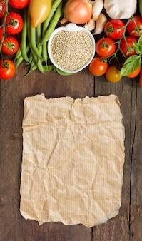 Quinoa in einer schüssel und frischem gemüse auf einer hölzernen tischoberansicht mit kopienraum