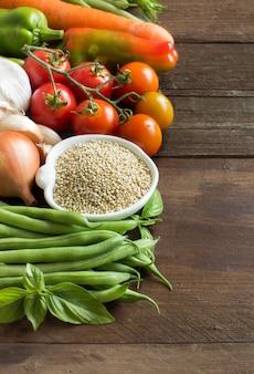 Quinoa in einer schüssel und frisches gemüse auf einem braunen holztisch schließen oben