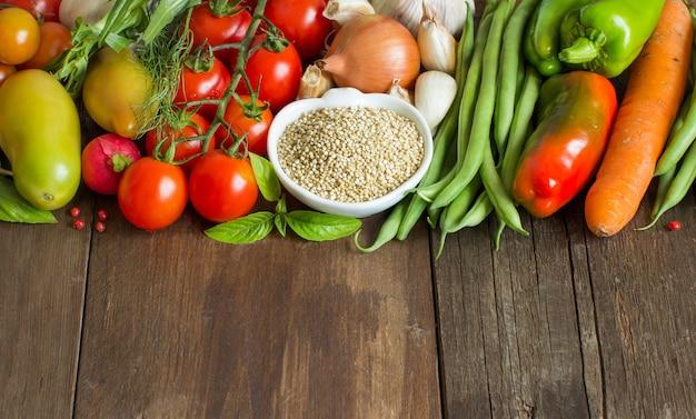 Quinoa in einer schüssel und frisches gemüse auf holztisch