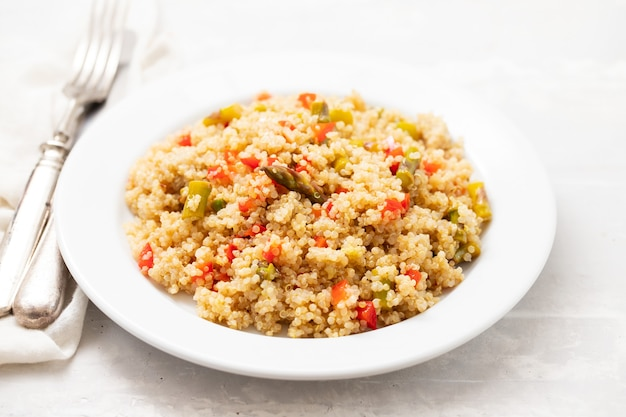 Quinoa mit gemüse auf weißem teller auf keramik