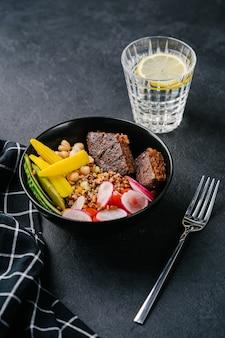 Quinoa mit saftigem veganem schnitzel, gurke, rettich, minimais und kichererbsen auf dunklem hintergrund