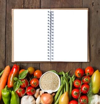 Quinoa, notizbuch und frisches gemüse auf einer braunen hölzernen tischoberansicht